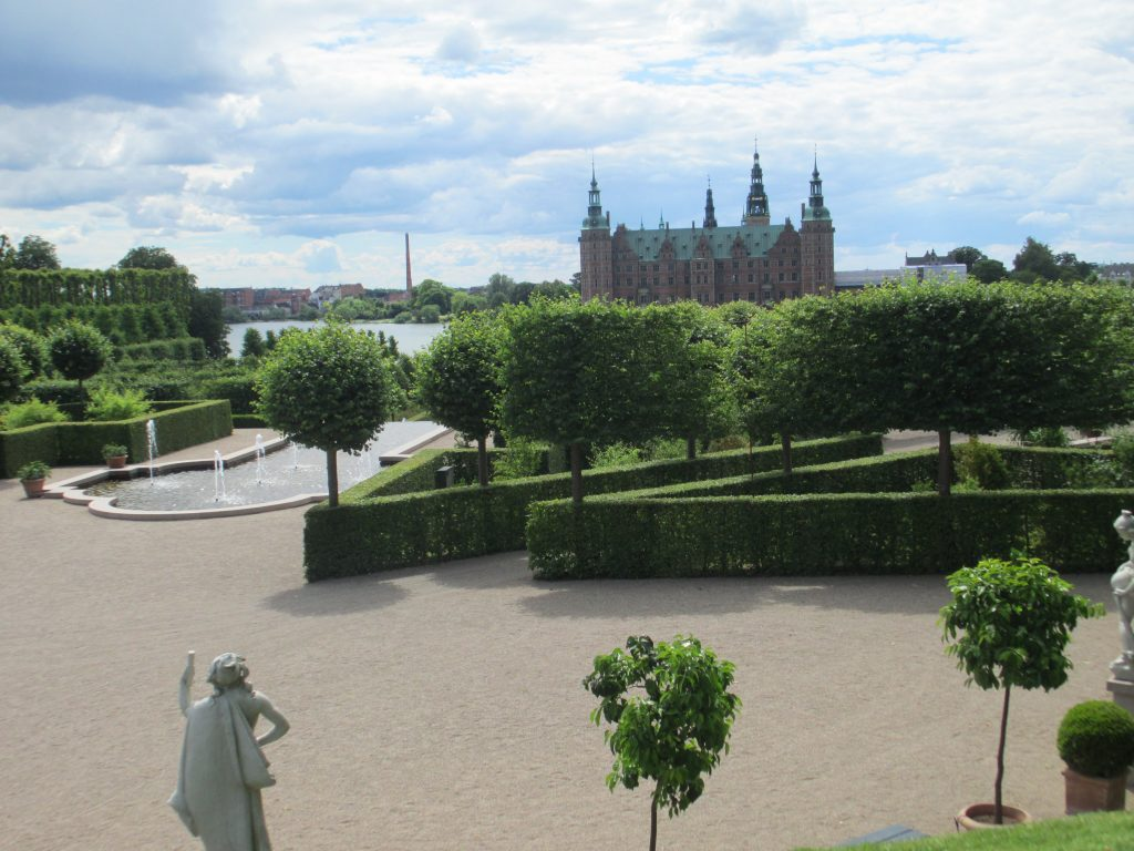 A view of Frederiksberg Palace, Denmark, a baroque palace in the background with hedges lining the walkways.