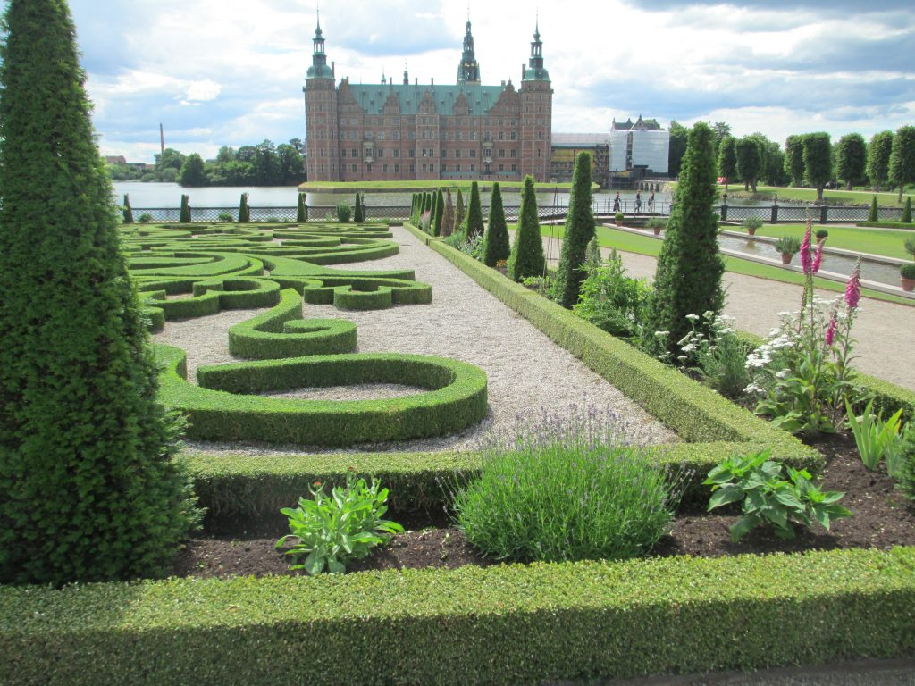 A view of Frederiksberg Palace, Denmark, a baroque palace in the background with a low hedge maze.