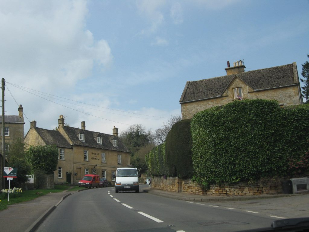 Tall, dense hedges along a roadway in England.